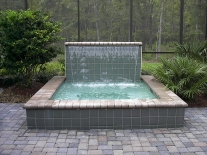 spa-with-raised-wall-and-sheer-descent-waterfall